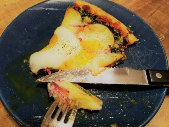 enjoying a slice of potato, kale, and egg pizza - yum!