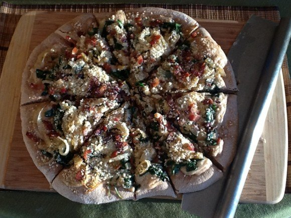homemade pizza with spinach, caramelized onion, and bacon