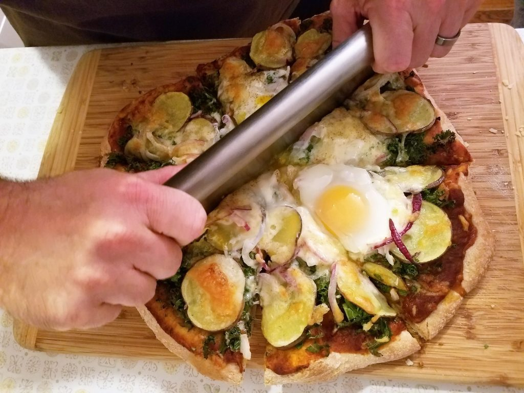 slicing up our homemade potato, kale, and egg pizza