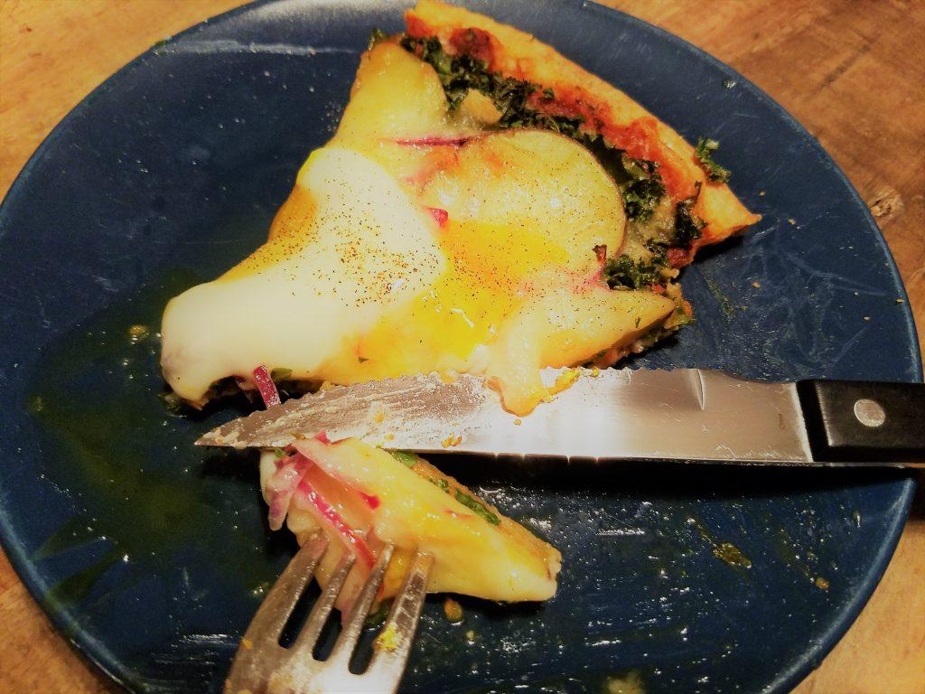 enjoying a slice of potato, kale, and egg pizza - yum!
